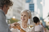 Affectionate senior couple holding hands drinking white wine at urban sidewalk cafe - HOXF00035