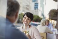 Smiling couple toasting white wine glasses at urban sidewalk cafe - HOXF00041