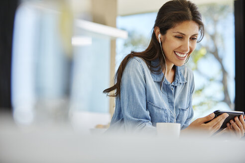 Smiling woman using digital tablet and headphones - HOXF00050