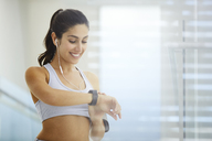 Woman exercising with headphones checking smart watch - HOXF00053