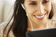 Close up smiling woman using digital tablet with headphones - HOXF00059