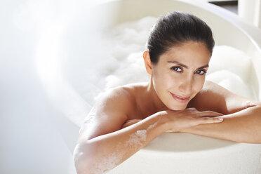 Portrait smiling woman enjoying bubble bath - HOXF00062