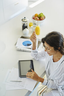 Woman in bathrobe working at digital tablet at kitchen counter - HOXF00065