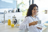 Smiling woman in bathrobe drinking coffee in morning kitchen - HOXF00068