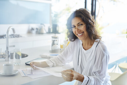 Portrait smiling businesswoman in bathrobe reviewing paperwork in kitchen - HOXF00071