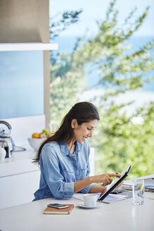 Woman working using digital tablet at kitchen counter - HOXF00074