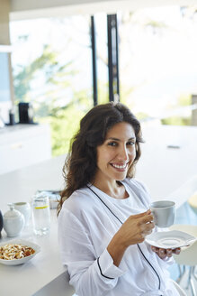 Portrait smiling woman in bathrobe drinking coffee in morning kitchen - HOXF00083