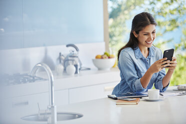 Smiling woman texting with cell phone at kitchen counter - HOXF00089