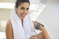 Portrait smiling woman with towel and water bottle listening to music with headphones post workout - HOXF00092