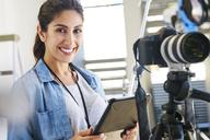 Portrait smiling female photographer using digital tablet behind camera in studio - HOXF00095