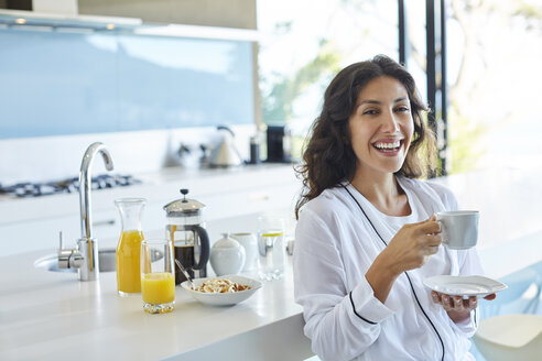 Portrait laughing woman in bathrobe drinking coffee in morning kitchen - HOXF00119