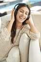 Carefree woman listening to music with headphones on sofa - HOXF00122