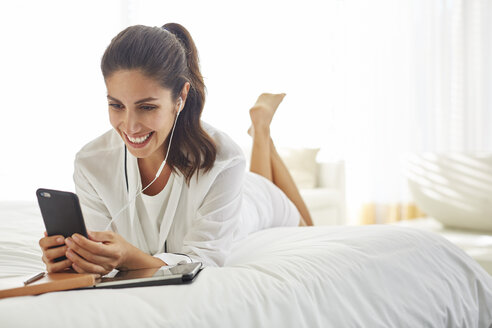 Smiling woman listening to music with headphones and mp3 player on bed - HOXF00125
