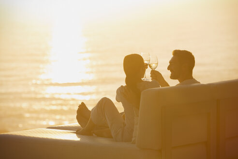 Silhouette couple toasting wine glasses on lounge chair with sunset ocean view - HOXF00134