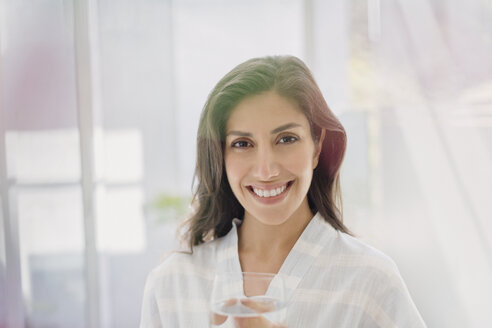 Portrait smiling brunette woman drinking water - HOXF00143