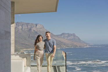 Smiling couple walking on luxury balcony with sunny ocean and mountain view - HOXF00149