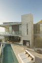 Couple standing on sunny modern luxury home showcase balcony over lap pool - HOXF00161