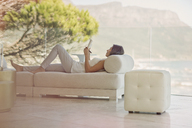 Serene woman doing crossword puzzle on chaise lounge on luxury balcony - HOXF00164