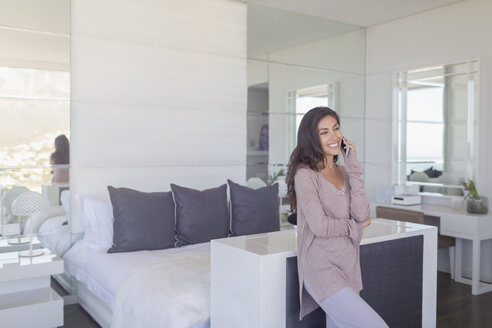 Smiling woman talking on cell phone in luxury modern bedroom - HOXF00179