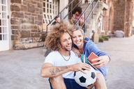 Couple with soccer ball taking selfie with camera phone - CAIF04199