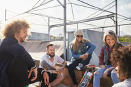 Friends hanging out and talking at sunny skate park - CAIF04220