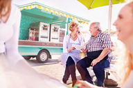 Smiling senior business owners using digital tablet outside food cart - CAIF04250