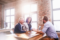 Smiling business people meeting at table in office - CAIF04268