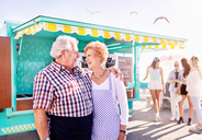 Smiling affectionate senior couple business owners outside sunny food cart - CAIF04274