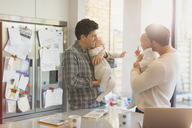 Male gay parents holding baby sons in kitchen - CAIF04298