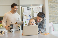Male gay parents and baby son using laptop and digital tablet in kitchen - CAIF04301