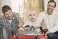 Male gay parents pushing baby son in toy car - CAIF04307