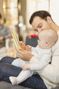 Father reading book to cute baby son - CAIF04310