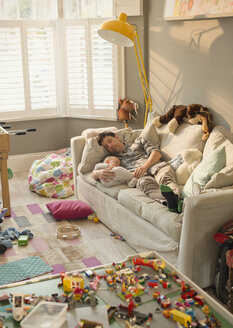 Exhausted father and baby son sleeping on sofa in messy living room with toys - CAIF04313