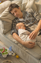 Exhausted father and baby son sleeping on sofa - CAIF04322