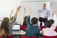 Male teacher calling on students in classroom - CAIF04373