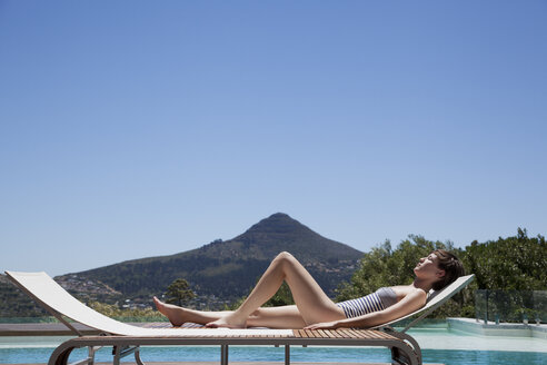 Woman sunbathing lounge chair poolside - CAIF04412