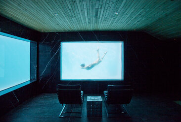 View of woman swimming underwater from window in pool room - CAIF04424