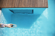 Woman in luxury swimming pool - CAIF04427