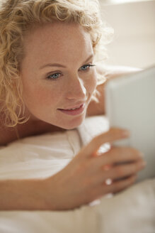Close up of woman laying in bed using digital tablet - CAIF04436