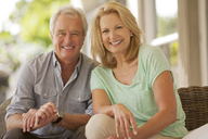 Portrait of smiling couple on patio - CAIF04442