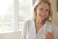 Portrait of smiling woman drinking glass of water - CAIF04451