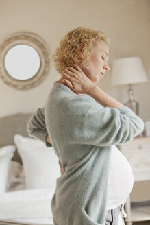 Pregnant woman holding neck and back in pain - CAIF04454