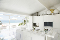 Modern living room overlooking beach and ocean - CAIF04466