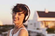 Portrait of smiling woman wearing headphones - CAIF04478