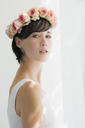 Portrait of serious bride wearing rose wreath on head - CAIF04487