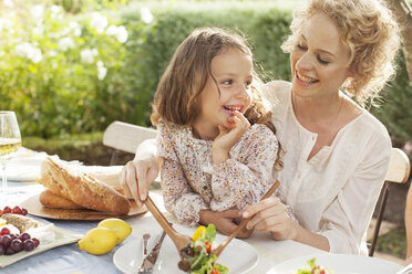Mother and daughter eating in garden - CAIF04532