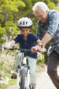 Grandfather teaching grandson to ride bicycle - CAIF04538