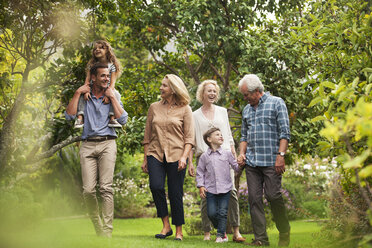 Multi-generation family walking together in park - CAIF04544