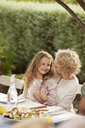 Mother and daughter sitting at table outdoors - CAIF04547