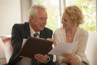 Financial advisor explaining paperwork to woman - CAIF04553